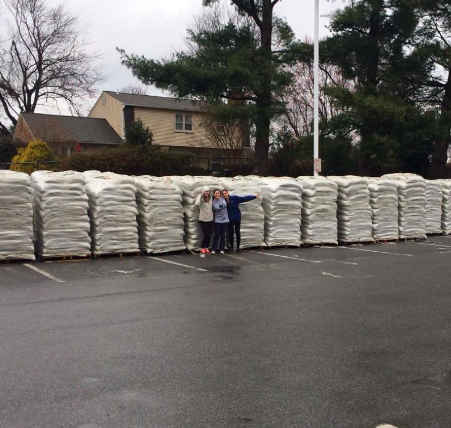 Students stand in front of piles of mulch to be delivered in the 2014 mulch sale.