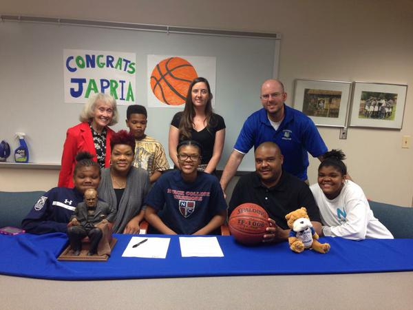 Karim-Duvall gathers with her family, coach Katelyn McMahon, Principal Joan Benz and athletic director Scott Rivinius to celebrate her commitment