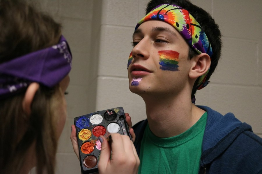 Senior Elanore Fuller paints rainbow on senior Michael Levine's face on CHS Unity Day.