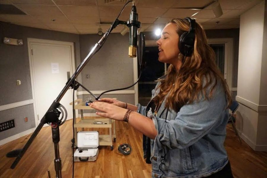 Alumna Kristina Hann works on her music in a recording studio. Hann is currently studying Music at Belmont University.