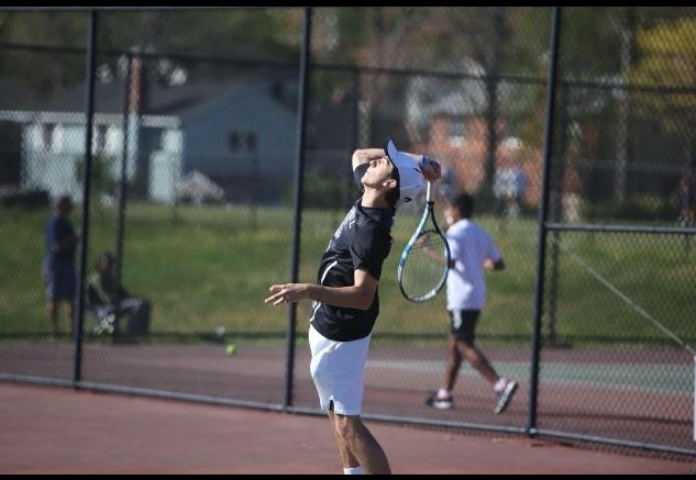 Senior Mark Dager serves the ball during a match. Dager and his doubles partner Austin Yang won their doubles bracket at counties.