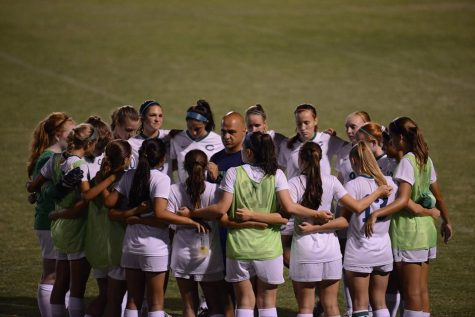 Before a game, the varsity girls soccer team huddles around their coach, Haroot Hakopian. Despite finishing third in the state, fewer CHS fans attend their games compared to the boys soccer games.