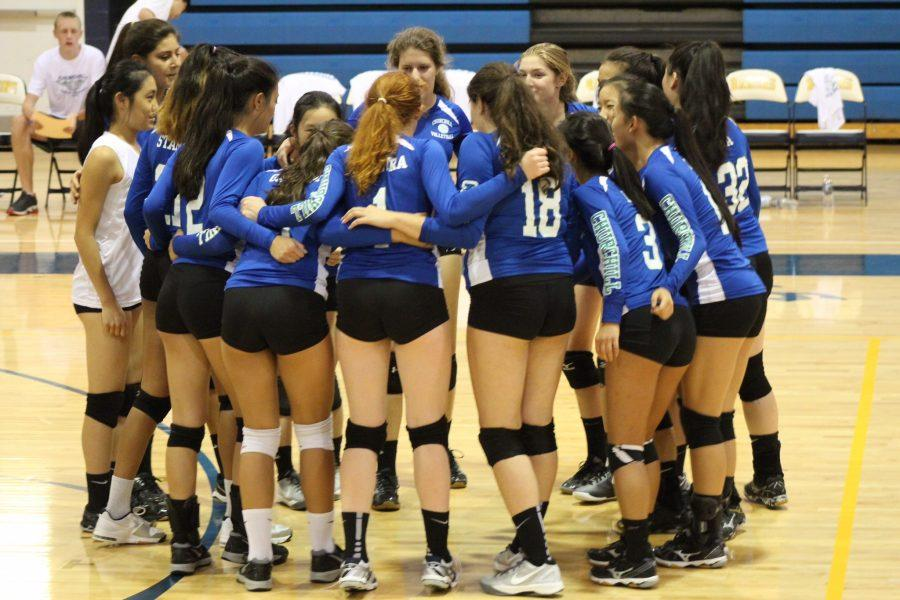 The girls varsity volleyball team meets in a huddle during a match. So far, the team is off to to a 5-0 start. Senior captains Emma Jin, Molly Stark and Nina Gautam have hopes of leading the team to States.