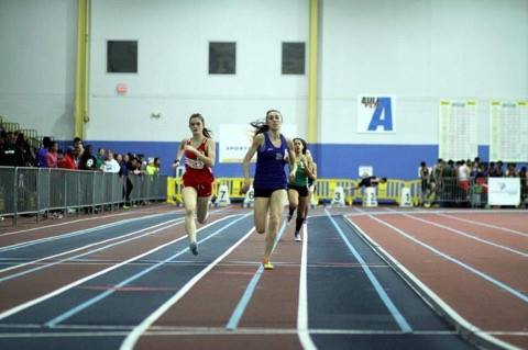Senior Gwen Asbury sprints down the track during an indoor track meet.