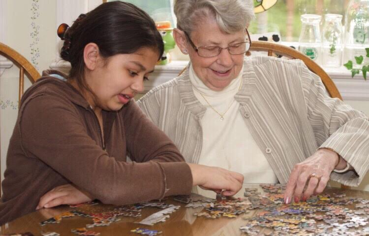 A+child+helps+an+elderly+woman+in+an+assisted+living+home+with+a+puzzle.