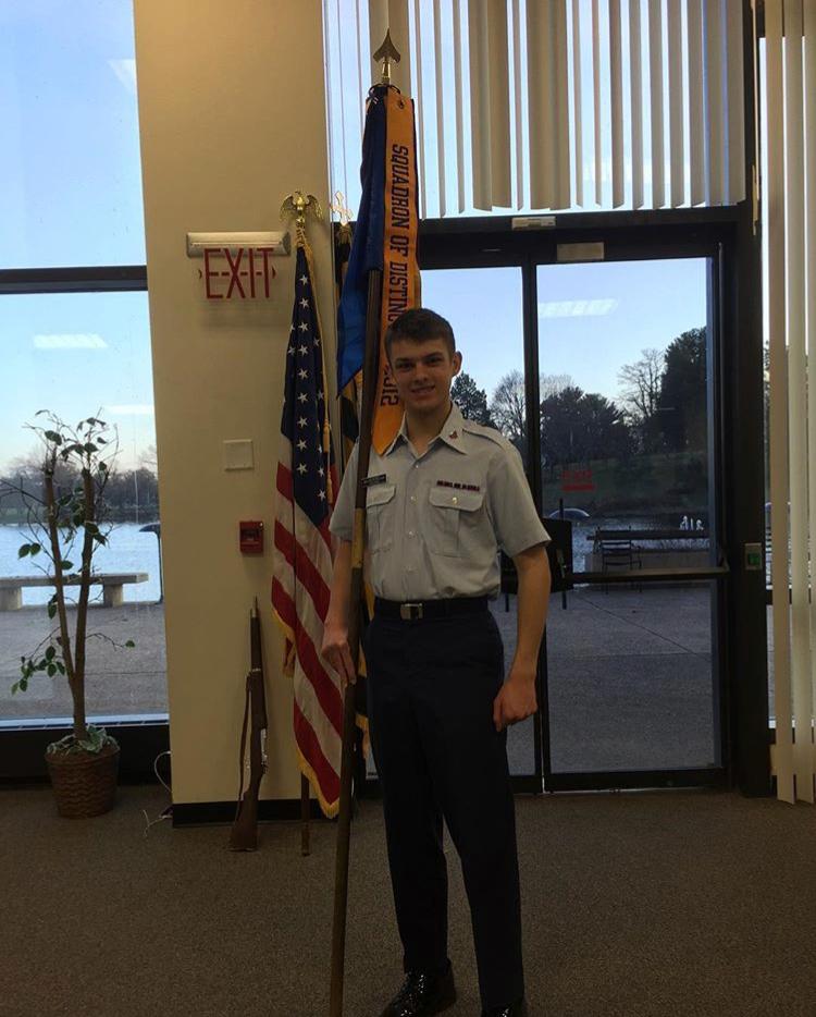Senior Patrick Cousins holds his squadron's flag.