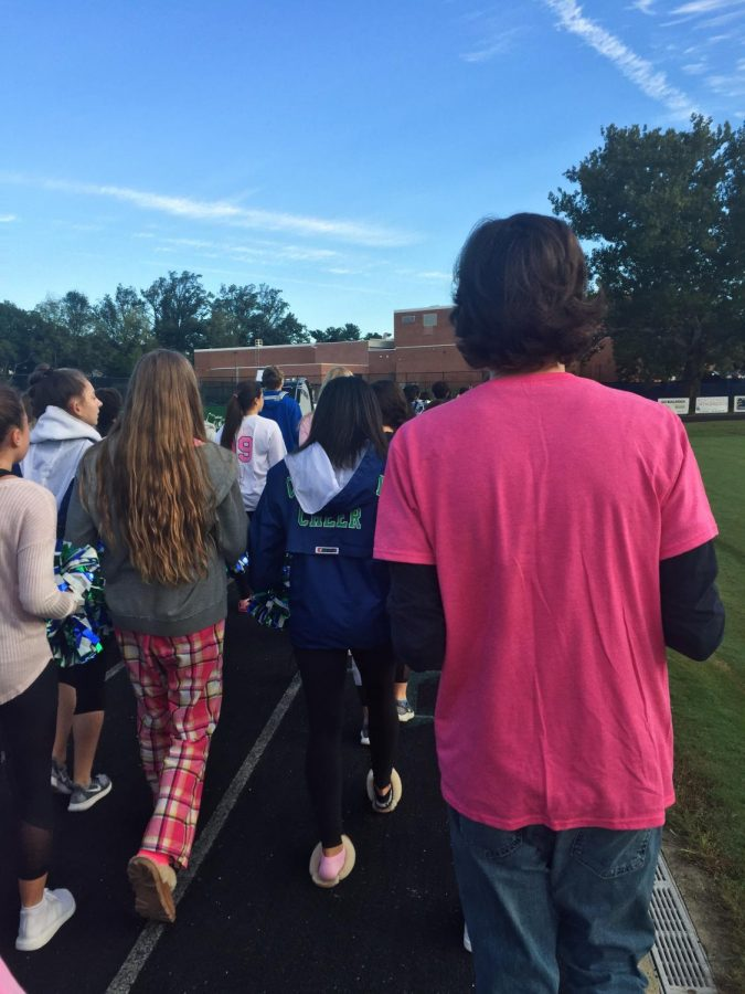 CHS+students%2C+including+Varsity+Cheer+and+the+drumline+walk+around+the+track+to+raise+Breast+Cancer+Awareness.