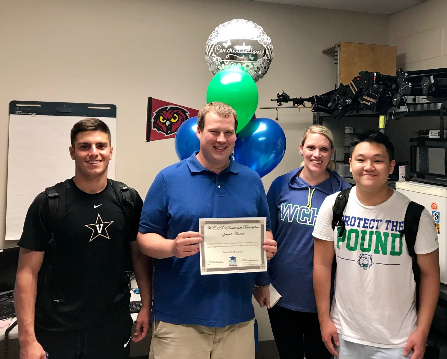 Senior Michael Janis, Technology director Benjamin Schnapp, Ms. Brandice Heckert, and junior William Ahn smiling for the camera just after Schnapp received the grant.
