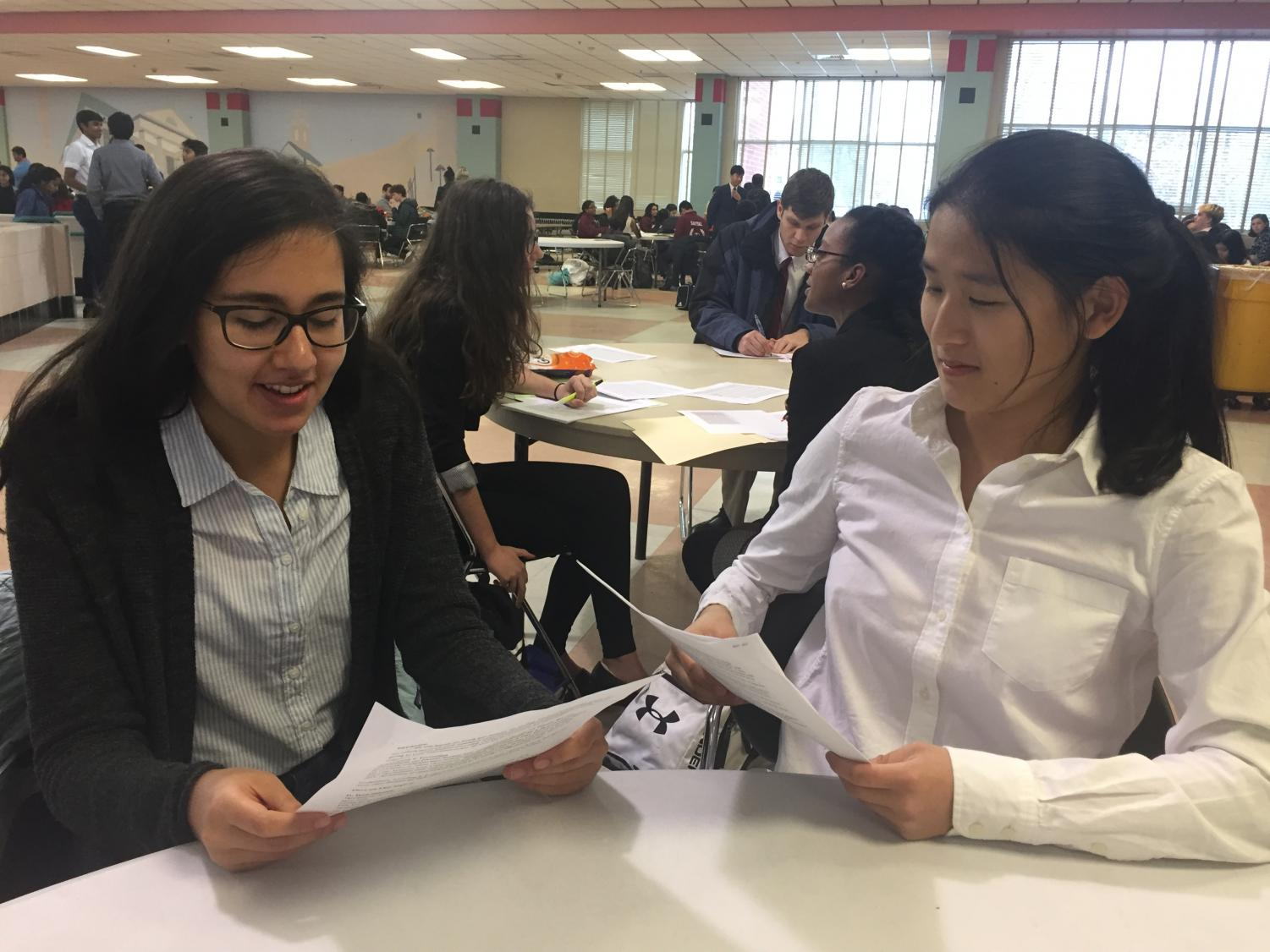 Sophomore Emily Tong and senior Janneke Kovoor practice their speaking points and plan their arguement at the Dec. 12 debate tournament at Blair High School.