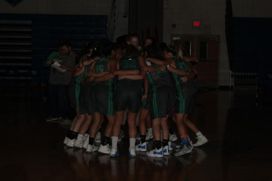 The+Varsity+Girls+Basketball+team+huddles+before+the+start+of+the+event.