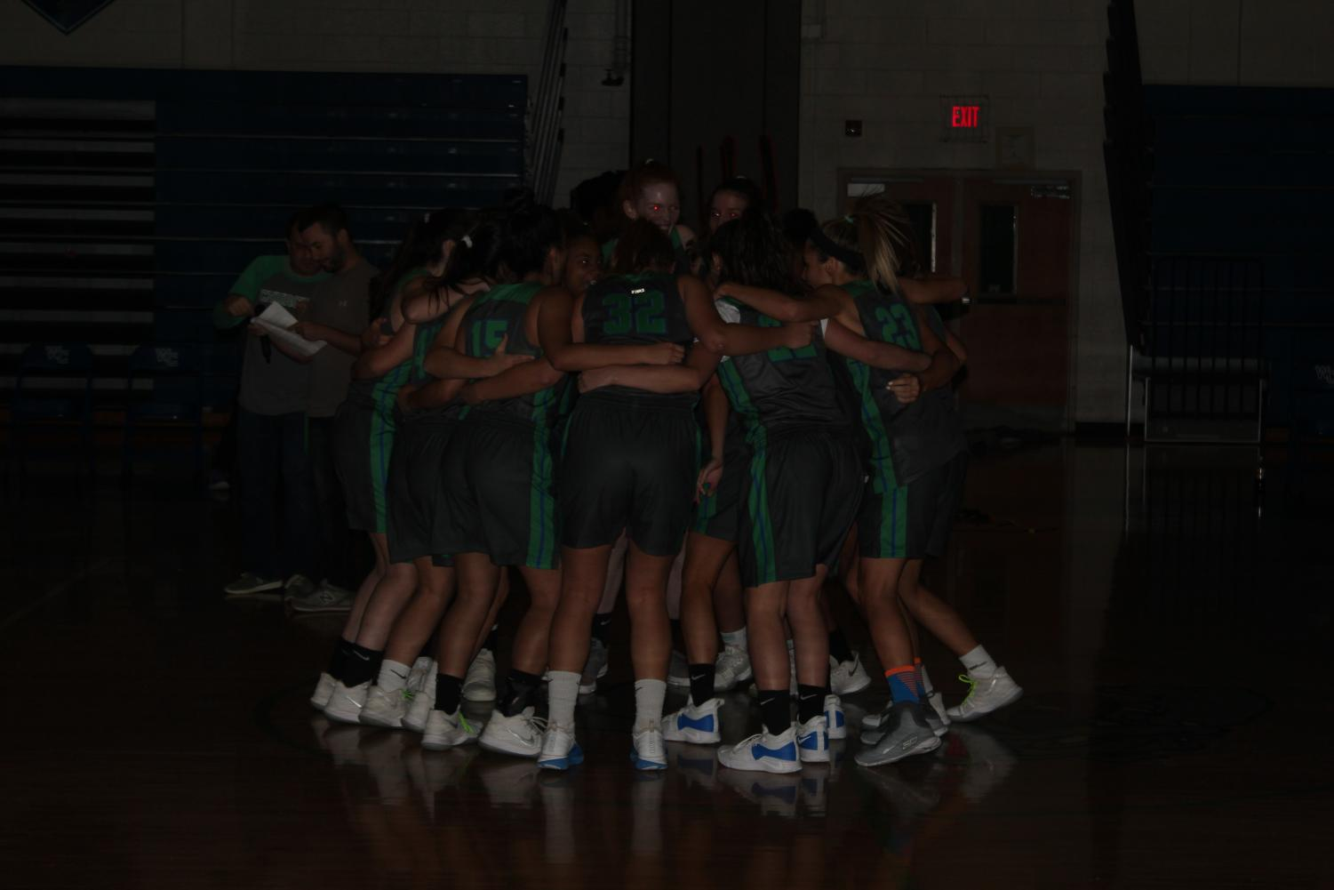 The Varsity Girls Basketball team huddles before the start of the event.
