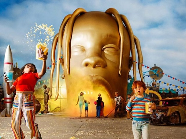 The+album+cover+shows+a+giant+gold+statue+of+Travis+Scott%E2%80%99s+head+as+the+entrance+to+an+amusement+park+with+children+and+parents+in+front+of+the+entrance.