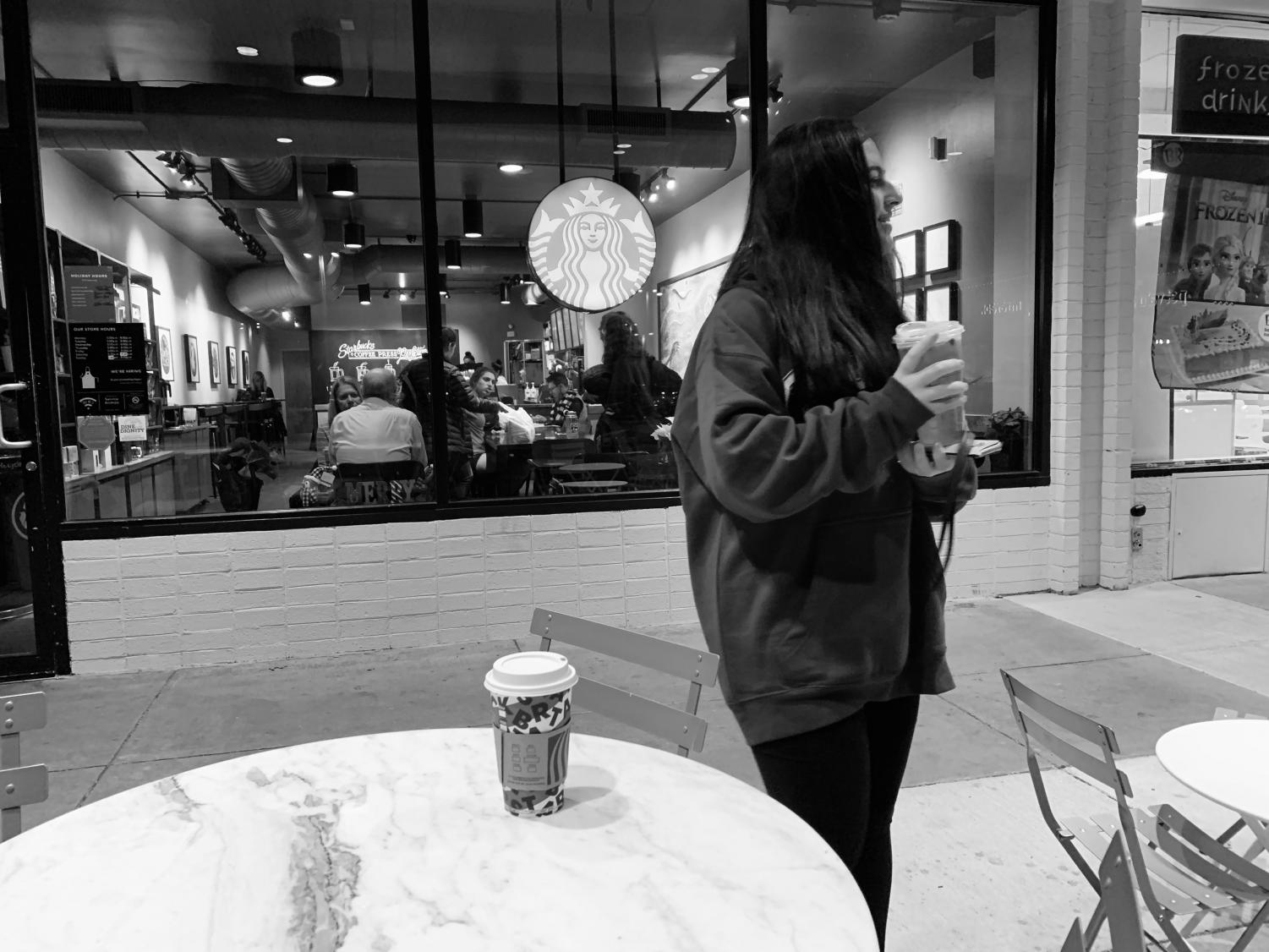 Sophomore Naz Yavuz stands outside of Starbucks at the Cabin John Shopping Center on a chilly night, drinking a hot and iced matcha latte from Starbucks.