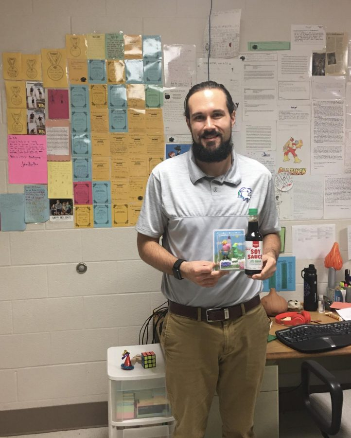 Mr. Antonucci stands in his office holding his gift of a Peppa Pig and the soysauce while he is surrounded by the written cards all over the walls.