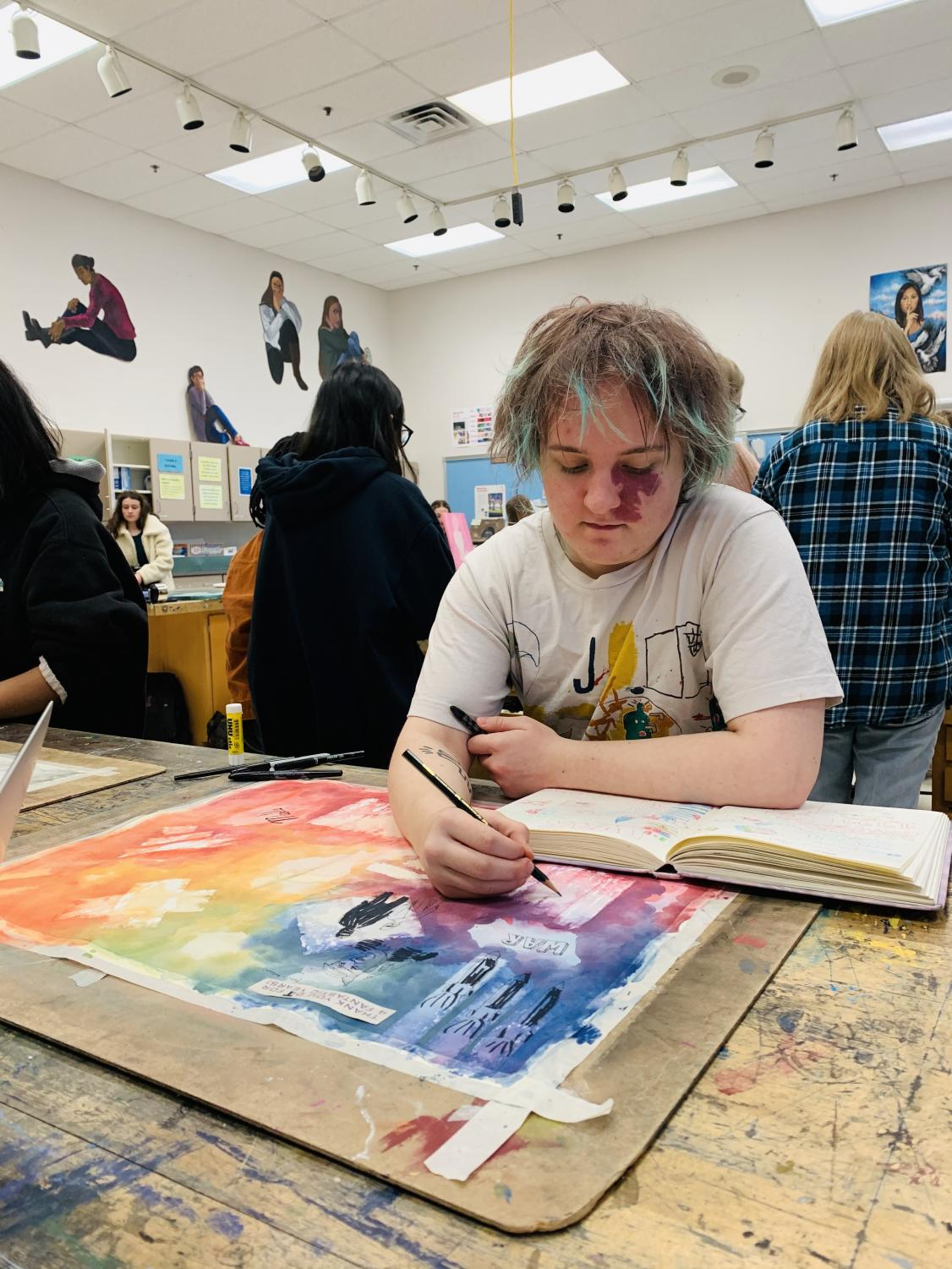 WCHS senior Markus Silvertree paints in his 4th period class, AP Art Studio, for his sustained investigation. On this large sheet, a compilation of ideas for new and potential pieces are mixed into one consolidated and designed brainstorming board.