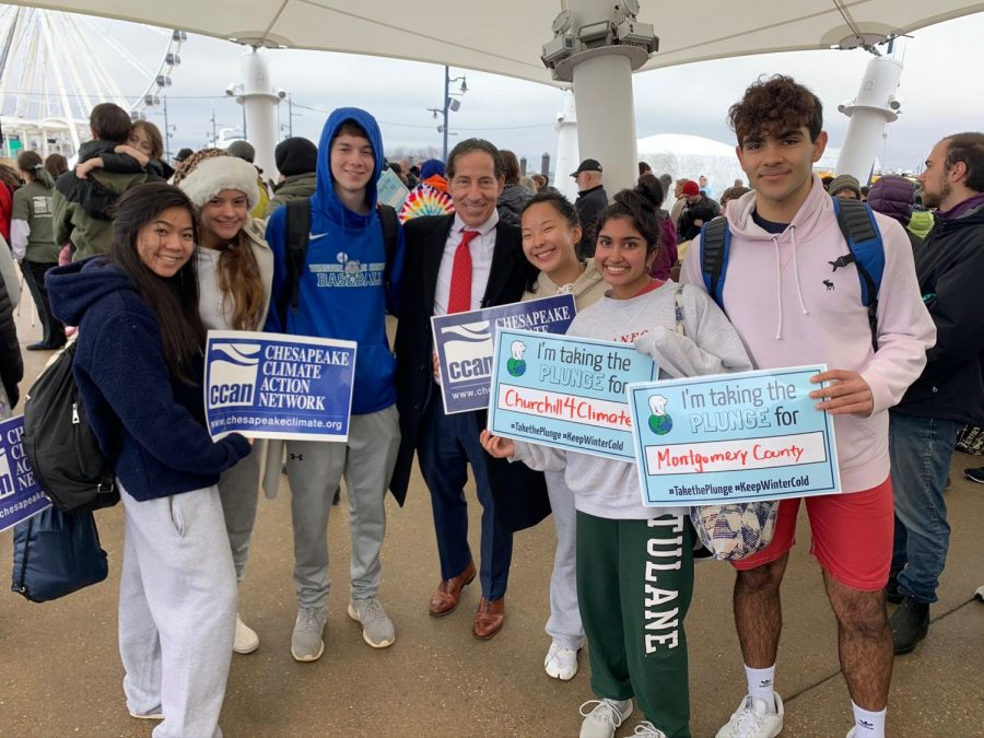 Churchill for Climate members smile with representative Jamie Raskin, as they hold posters with reasons as to why they participated in the polar plunge