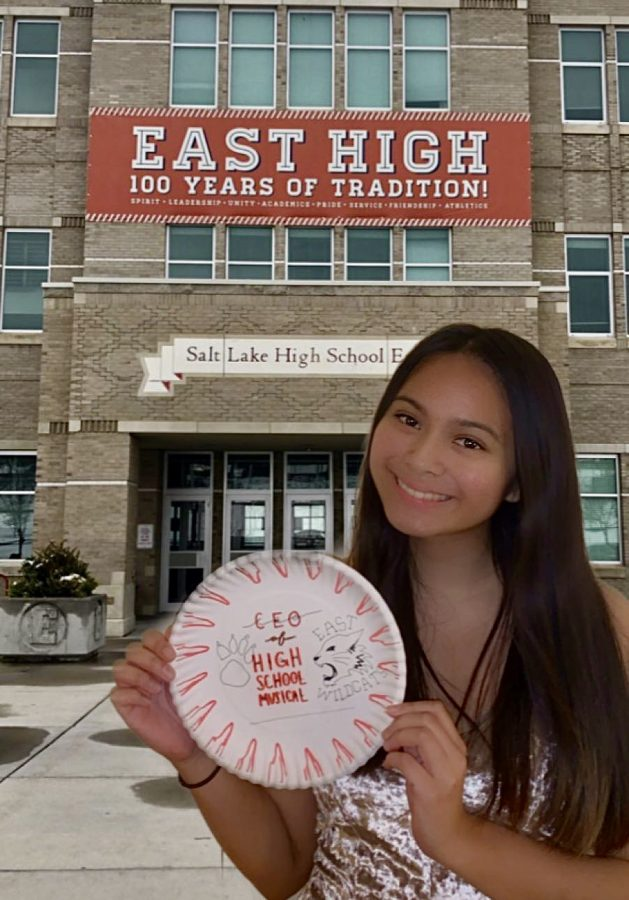 "Senior Hannah Zozobrado poses at ""East High,"" the fictional high school from the ""High School Musical"" franchise. She holds up a paper plate, a signature activity of many banquets."