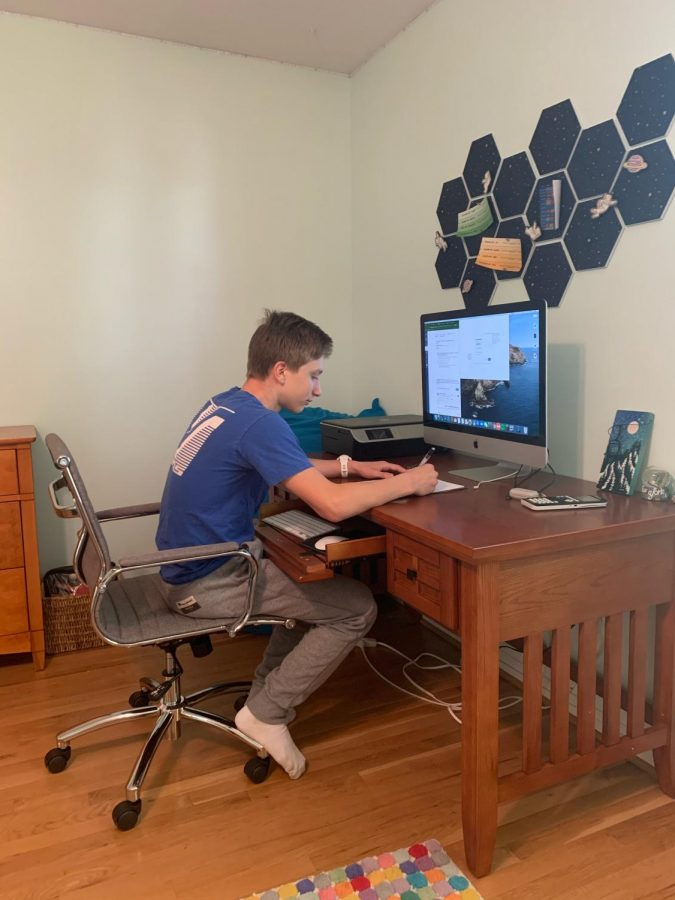 "Josh Heimlich sits at his workspace in his house after a day of online school and works on his new assignments.  ""I enjoy having the freedom to choose where I want to work based on how productive I will be,"" said Josh.  Josh has been working in this office for the past few months because he has been productive here."