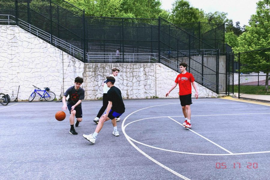 Dribbling a basketball towards a defender, Zack Mantz (left) plays basketball during his freetime at Cabin John Middle School against some of his closest friends.