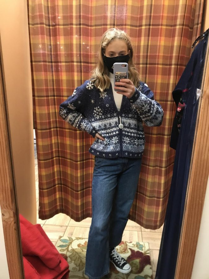 Junior Callie Burd poses in the dressing room of a thrift store with her new finds. Burd has been thrifting for almost three years and loves finding unique items and being eco-friendly.