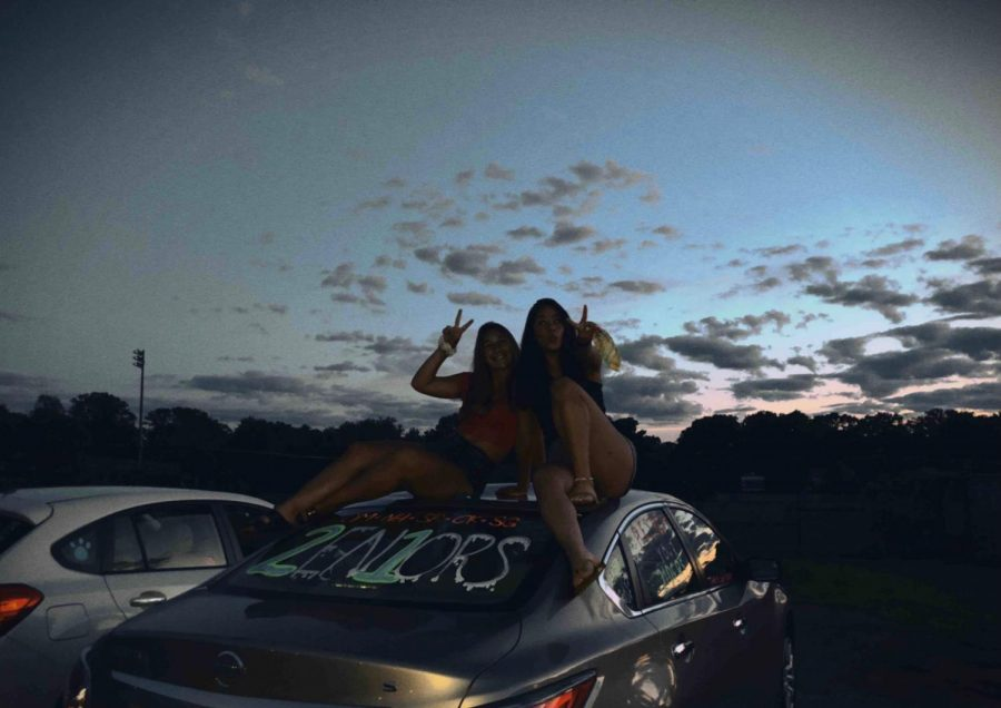 Olivia Meshanko and Natalie Heshmat pose on top of a newly decorated car. Shoshana Rosenthal has been using an app that emulates a disposable cameras in order to make lasting memories with her friends.