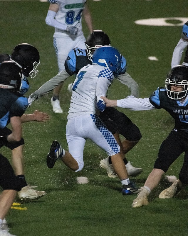 WCHS Senior Jeffrey Yee weaves between two Whitman defenders after catching a pass during the first game of the Bulldog's season.