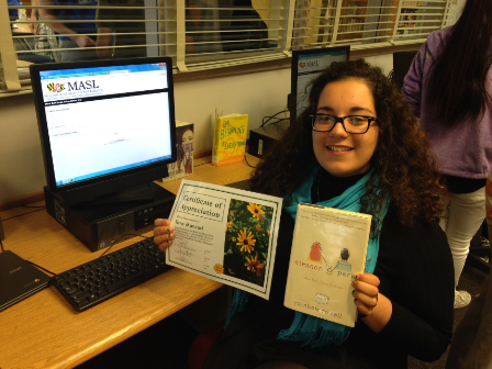 Sophomore Tara Manzari holding up her favorite BES book and her certificate for having read at least three books.