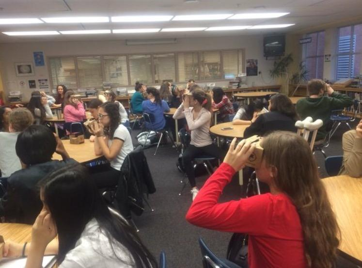Students in the media center use Google Cardboard to travel to  virtual destinations.