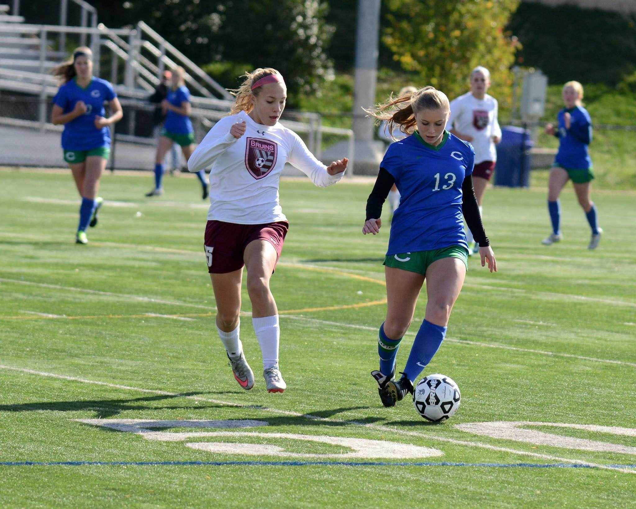 Senior Juliana Comer (right) dribbles past a defender in the state semifinal game.