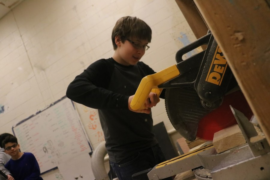 Freshman Ethan Finke uses tech power tools to cut a piece of wood that will help finish the set design.