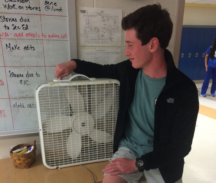 Freshman Ian Rosenthal uses a fan to cool himself off during the school day as a substitute for air conditioning.