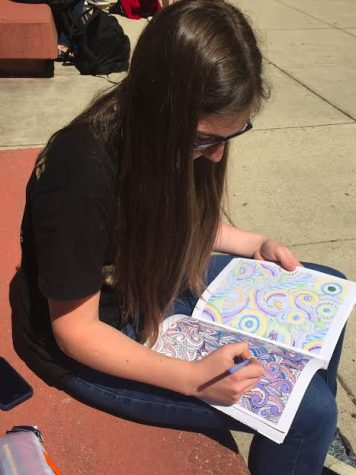 Freshman Emma Gray relaxes with an adult coloring book.