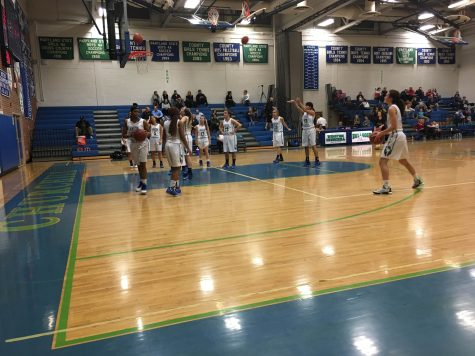 The varsity girls basketball team warms up before the second half of their home game against Wootton. Head Coach Katelyn Blanken talks privately with each player to discuss the results of their tryout, whether or not she made the team.