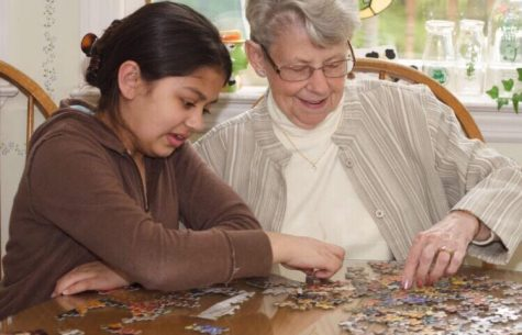 A child helps an elderly woman in an assisted living home with a puzzle.