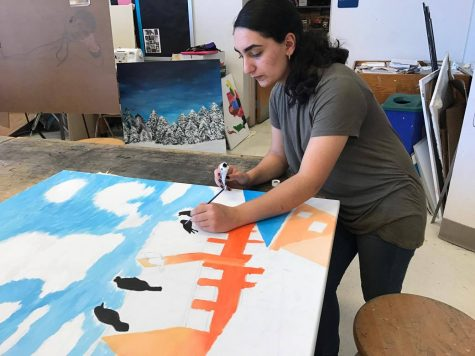 Senior Laudan Nikoobakht paints birds sitting on a wire for this year's Youth Art for Healing project.