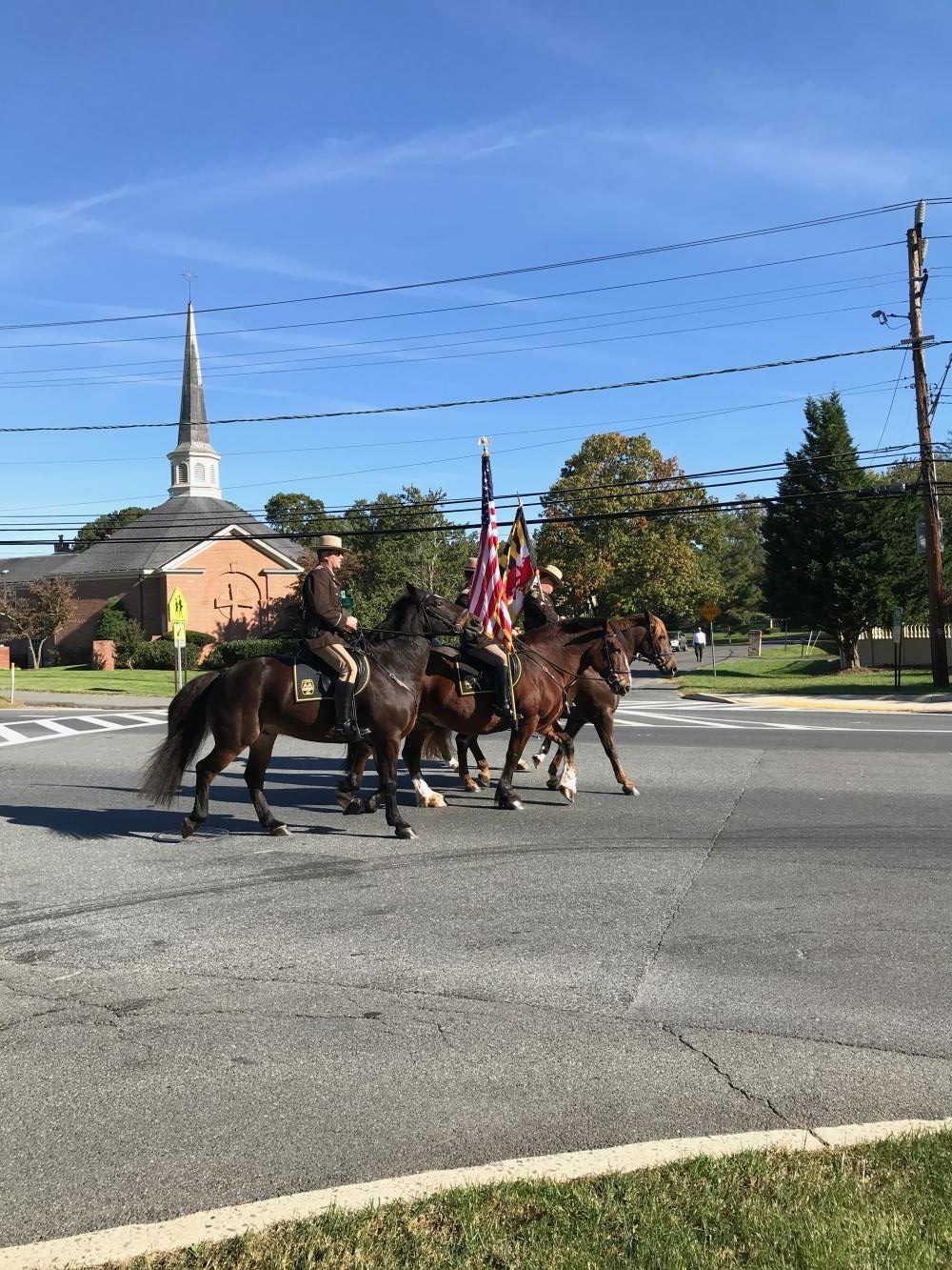 Policemen on horses lead the Parade, holding the colors of Maryland and the U.S.