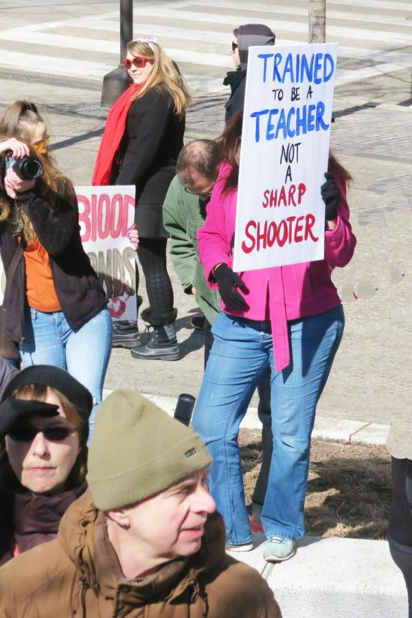 Teachers at a March 2018 protest hold up signs against the proposal of a law that mandates school teachers to be armed.
