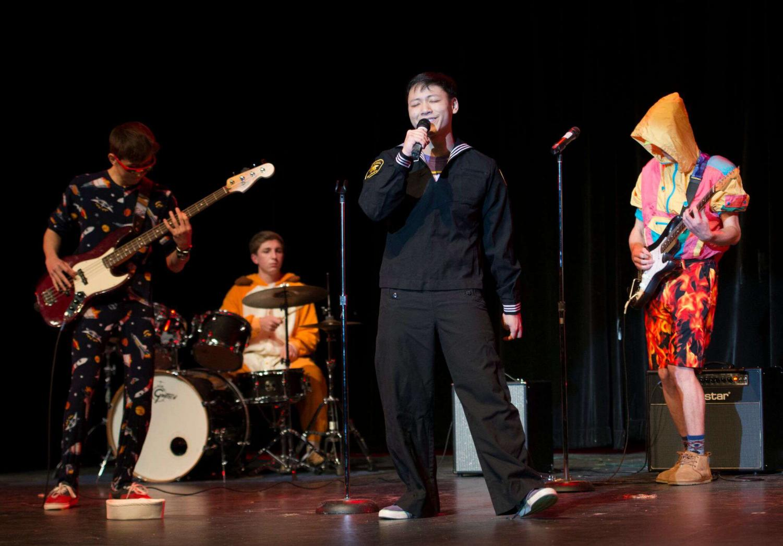 Tam, center, accompanies his band,