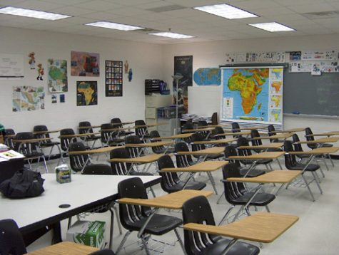 The stereotypical classroom of wooden desks and chairs awaits high school students.