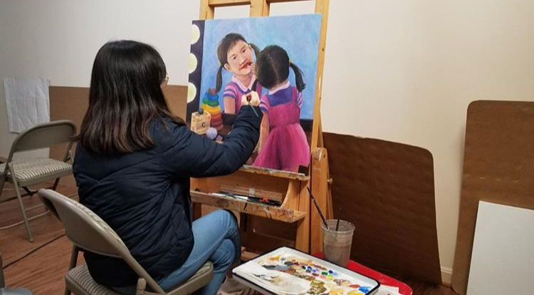Artist Claire Yang at work, painting on canvas for John's Hopkins's art competition.