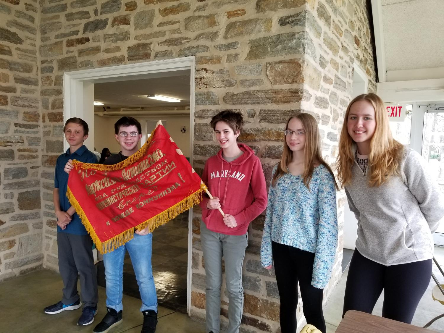 (Left to right) Jackson Will, Amiel Bengert, Gloria Herman, Veronica Starchenko and Anastasia Avrine, all level 3 Russian students, stand with a Russian Soviet Flag at Russian Olympiada.