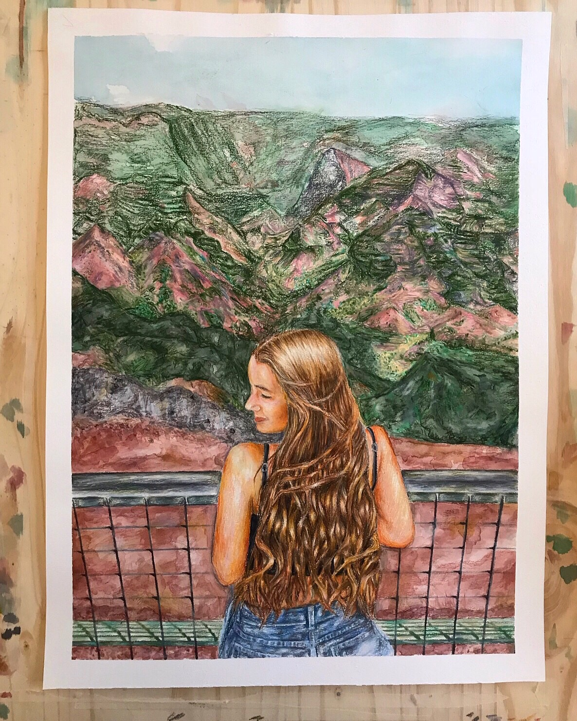 Elizabeth Kronthal's self portrait with a background of a cluster of mountains.