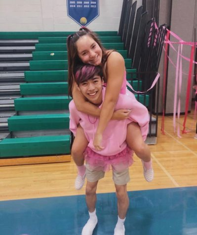 Haley Gye and Aiden Sung smile as they model bright pink to raise awareness about the Dig Pink game and the cause.