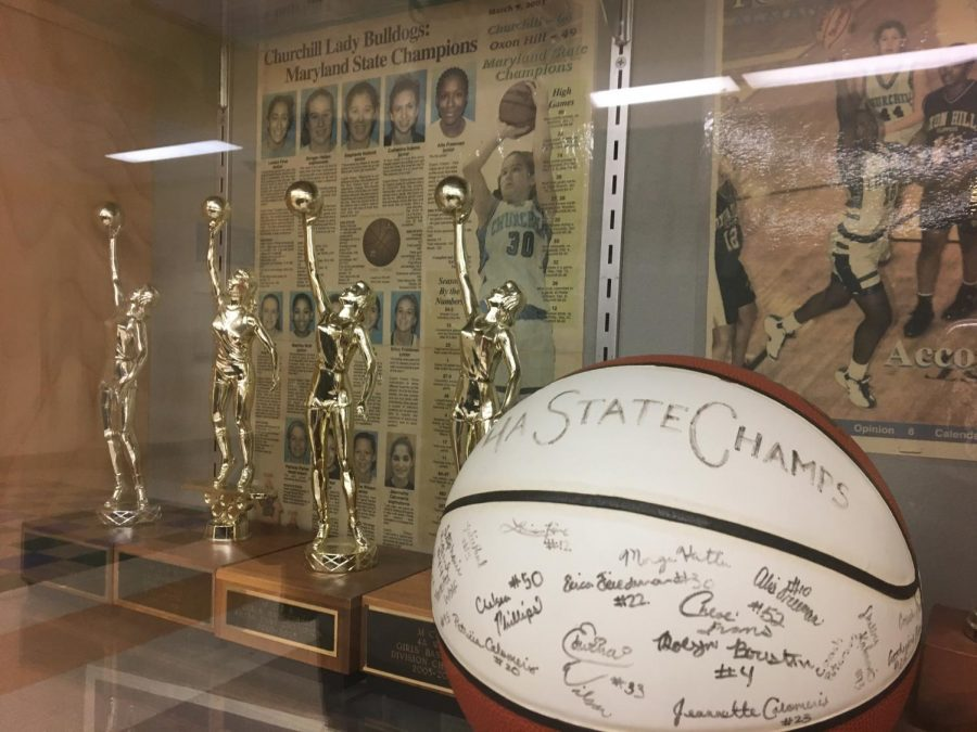 The+state+championship+trophies+of+the+WCHS+girls+varsity+basketball+team+displayed+proudly+in+front+of+a+news+article+snippet+from+2002+announcing+the+team%27s+success.+