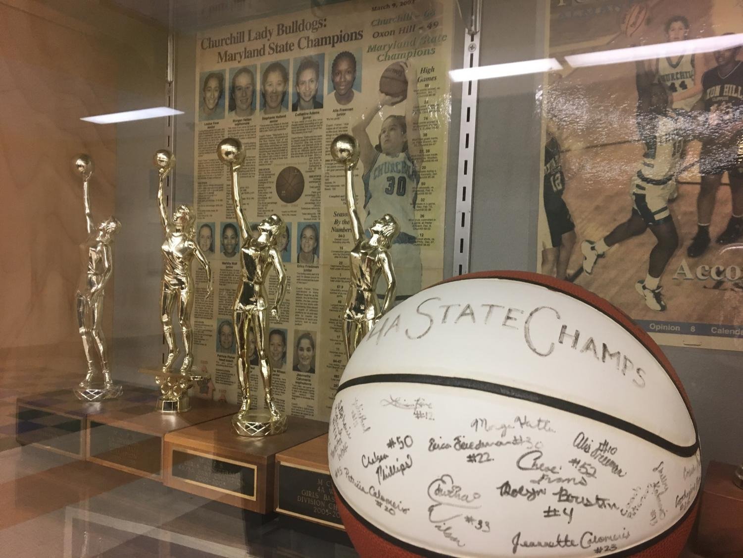 The state championship trophies of the WCHS girls varsity basketball team displayed proudly in front of a news article snippet from 2002 announcing the team's success.