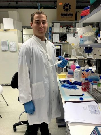Dressed up in his white lab coat and blue gloves, Nathan Slotnik makes the most of his SciTech Scholarship as he holds a micropipette in the laboratory, ready to contribute to finding a cure for Duchenne muscular dystrophy.