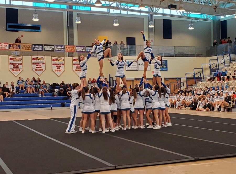 The WCHS cheer team stunts at the MCPS regional competition. The team has been practicing these elaborate tricks all season.