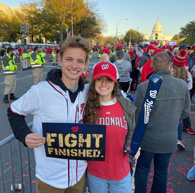 "Senior Jeremy Ashe (left) stands along Constitution Ave. for the Nationals ""Nats"" Parade, sporting the baseball team in support of their recent World Series win."