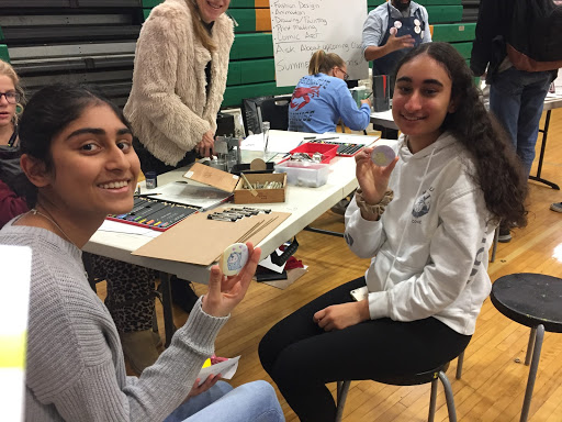 Sophomores Arya Iyer (left) and Sonia Bhatia talking to a staff member from the Stone Branch School of Art. She helped them make buttons - the pair made narwhal buttons, that they colored in on a piece of paper, that was then pressed against the button.