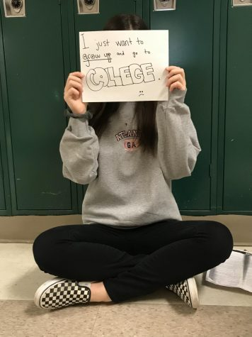 "Sophomore Aliki Dimitoglou holds up a paper that says ""I just want to grow up and go to college,"" reflecting the general attitude of many students at WCHS."